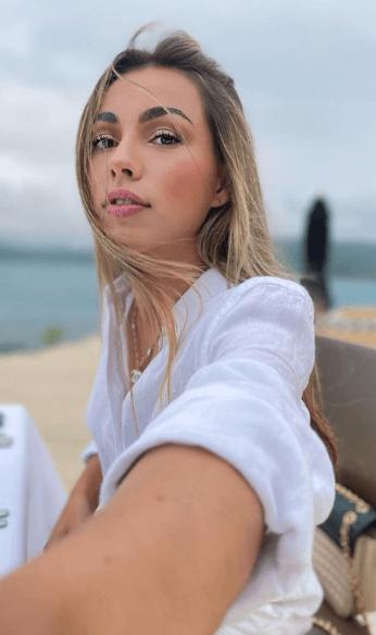 Mila wearing white top